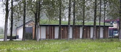 gebouw met groen dak tussen de bomen